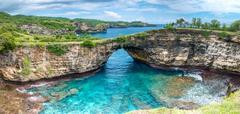Rock coastline. Stone arch over the sea. Broken beach, Nusa Penida ,Indonesia Stock Photos