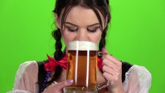 Oktoberfest girl flirting and drinking beer from a glass. Green screen. Slow Stock Footage