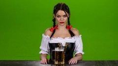 Girl in Bavarian costume celebrates Oktoberfest beer drinkers and beckons. Green Stock Footage