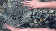 Slow motion, 120fps, of woman hands, play with transparent water Stock Footage