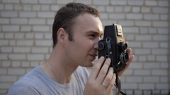Man taking pictures with vintage camera. Brick wall in the background. Stock Footage