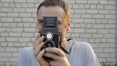 Photographer using a retro old camera. Brick wall in the background. Stock Footage