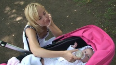 Mum feeds the baby milk formula from a bottle in stroller at street Stock Footage