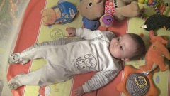 The baby lies on back and turned over on stomach in a playpen with toys Stock Footage