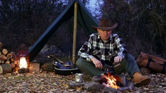 4K.Man   in cowboy hat  near  bonfire make coffee. Autumn travel life.  Stock Footage