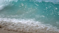 Slow motion, 240fps, of green sea wave with vibrant splash on brown sand beach Stock Footage