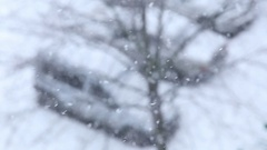Heavy snowfall in city. Top view of blurry three automobiles on parking Stock Footage