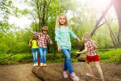 Happy kids walking on log and balancing in forest Stock Photos