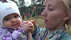 Baby feeding apple mom outside in the park Stock Footage