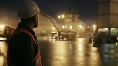 Engineer in hardhat with a tablet computer looks at truck on heavy industry Stock Footage
