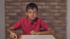 Child sitting at the desk holding flipchart with lettering signature on the Stock Footage