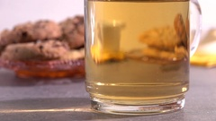 Putting tea strainer in glass teacup. Table with cookies in the background. Stock Footage