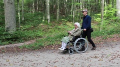 Caregiver and senior lady in a wheelchair during walk in park Stock Footage