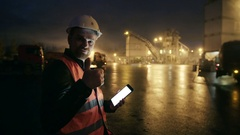 Engineer with tablet computer looks at camera at heavy industry factory Stock Footage