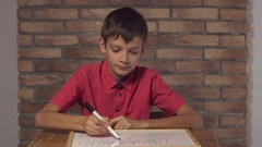 Child sitting at the desk holding flipchart with lettering million on the Stock Footage