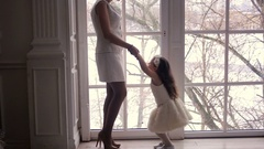 Mother and daughter three years sitting by the large window Stock Footage