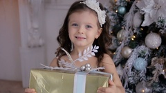 Little girl in a white dress holds a new year's gift Stock Footage
