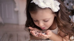 Little girl three years blowing on silver sequins Stock Footage