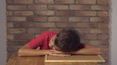 Child sitting at the desk holding flipchart with lettering wake up on the Stock Footage
