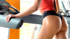 Athlete girl trains the buttocks on the simulator Stock Footage