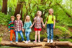 Five friends standing holding hands on log bridge Stock Photos