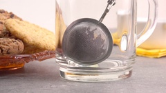 Pouring hot water in glass teacup with strainer. Slow motion film clip. Stock Footage