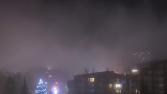 Fog clouds moving quickly over hotels and blocks of flats with nightfa Stock Footage