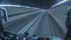 Timelapse with a bus crossing a road tunnel under a mountain behind. Stock Footage