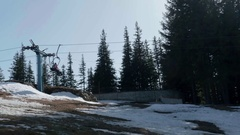 Pair of lovers who descend chairlift on a slope that melted snow. Stock Footage