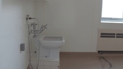 Abandoned hospital - pan from toilet to window Stock Footage