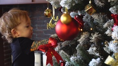 Little Boy touches Toy On Christmas Tree. 4k Stock Footage