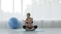 Beautiful pregnant girl with a big belly is dancing in the fitness room sitting Stock Footage