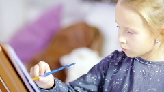 Adorable little girl painting a picture on easel indoor Stock Footage