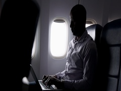 African American passenger silhouetted with laptop on aircraft MLS 4K Stock Footage