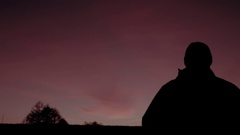 Silhouette of stalker at sunset sky background in post-apocalyptic world Stock Footage