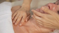 Woman middle-aged take face and neck lymphatic, drainage massage in spa salon Stock Footage