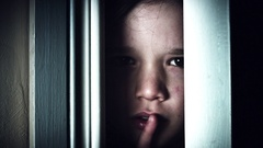 4K Thriller Child Eye Looking through Door Gap and Shows Shush Stock Footage