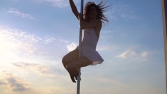 Sexy attractive girl poledancer performs advanced pole dance tricks at sunset on Stock Footage