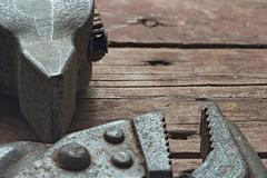 Hammer and adjustable wrench on a rough wooden background Stock Photos
