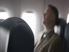 Airline passenger relaxes in main cabin of commercial flight 4K Stock Footage