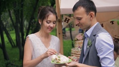 Bride and groom eat cake from one plate in front of trolley with sweets Stock Footage