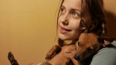 Smiling teen girl having fun with her little toy terrier doggy. 4K UHD Stock Footage