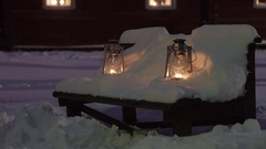 Two gas lanterns on a bench covered in snow Stock Footage