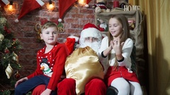 Bad girl and boy with the good behavior of sitting on the lap of Santa Claus Stock Footage