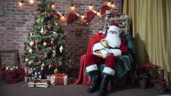 Santa Claus sitting in a chair near a Christmas tree meets children. Slow motion Stock Footage