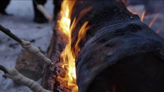 Roasting dough in open flame from a Swedish Torch Stock Footage