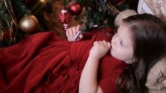 A little girl three years in a red dress lipstick lying Stock Footage