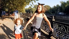 SLOW MOTION. Cute kids brother and sister walking by the river in the city park Stock Footage