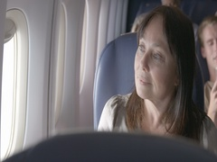 Mature female passenger looks out of airplane window on commercial flight MS 4K Stock Footage