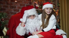 Closeup girl posing sitting on the hands of Santa Claus Stock Footage